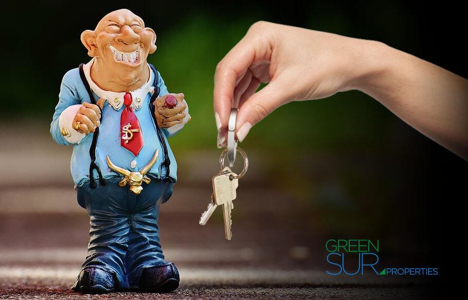 Shady businessman, hand dangling house keys.