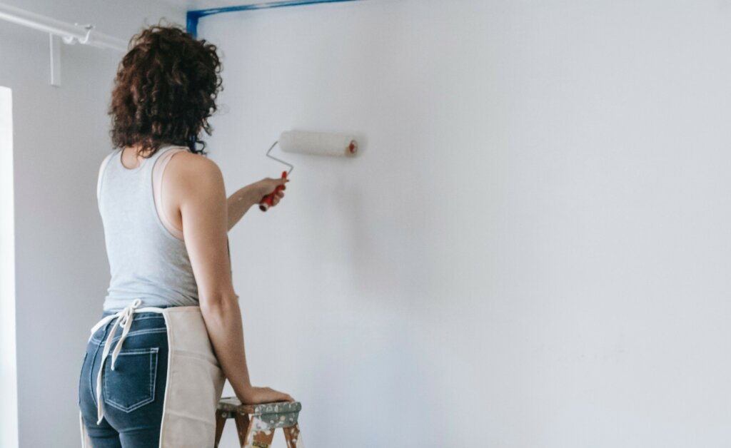 woman repainting the walls white before selling the house