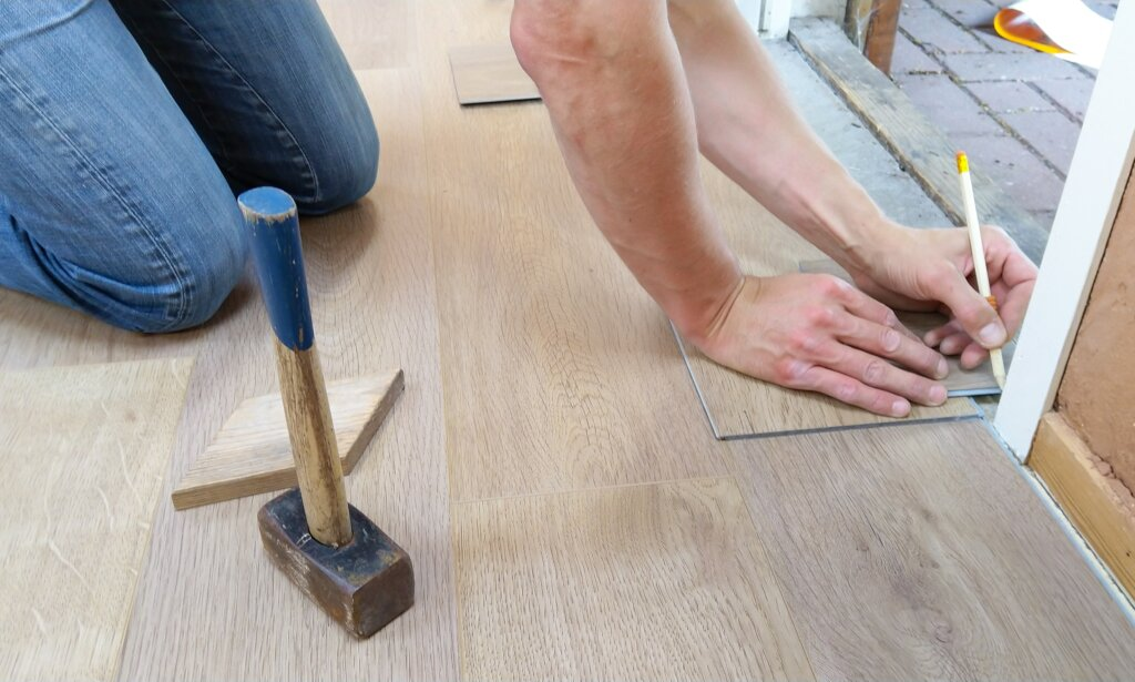 man measuring the space to place the wooden floorloor