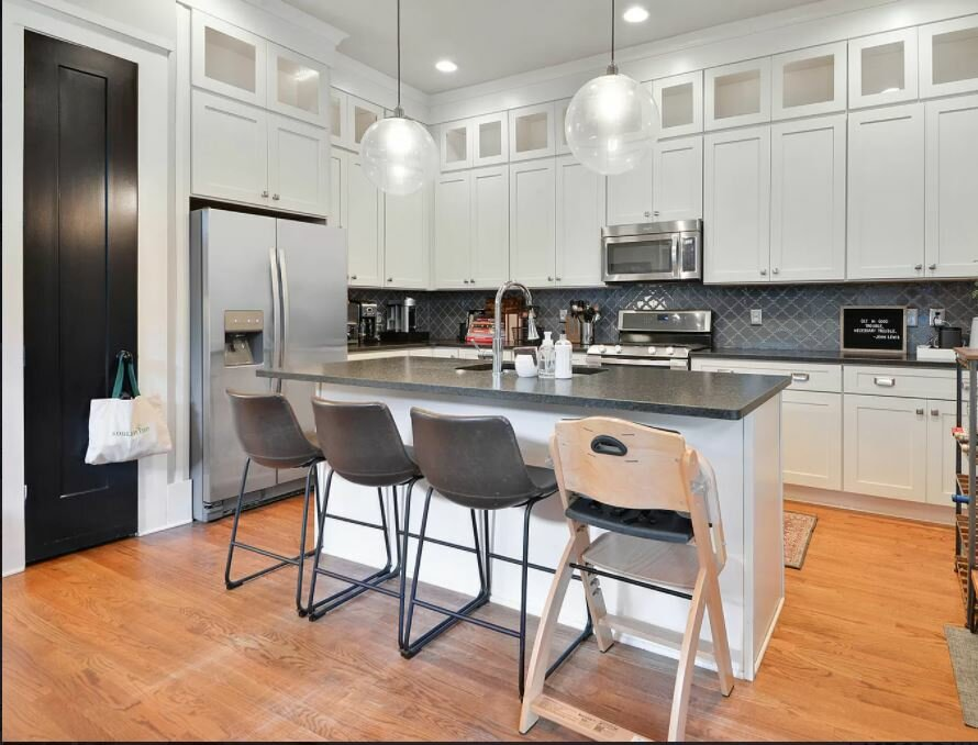 Kitchen with white shaker cabinets, island with grey counters, grey chairs, stainless appliances, hardwood floors
