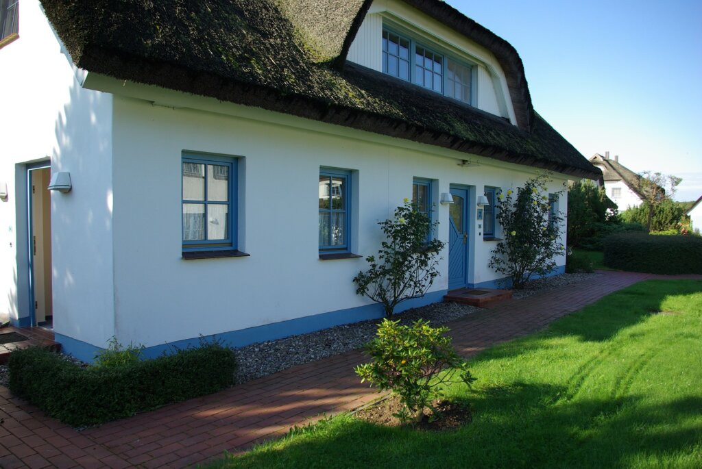white rental property with blue window trim and doors. Green grass