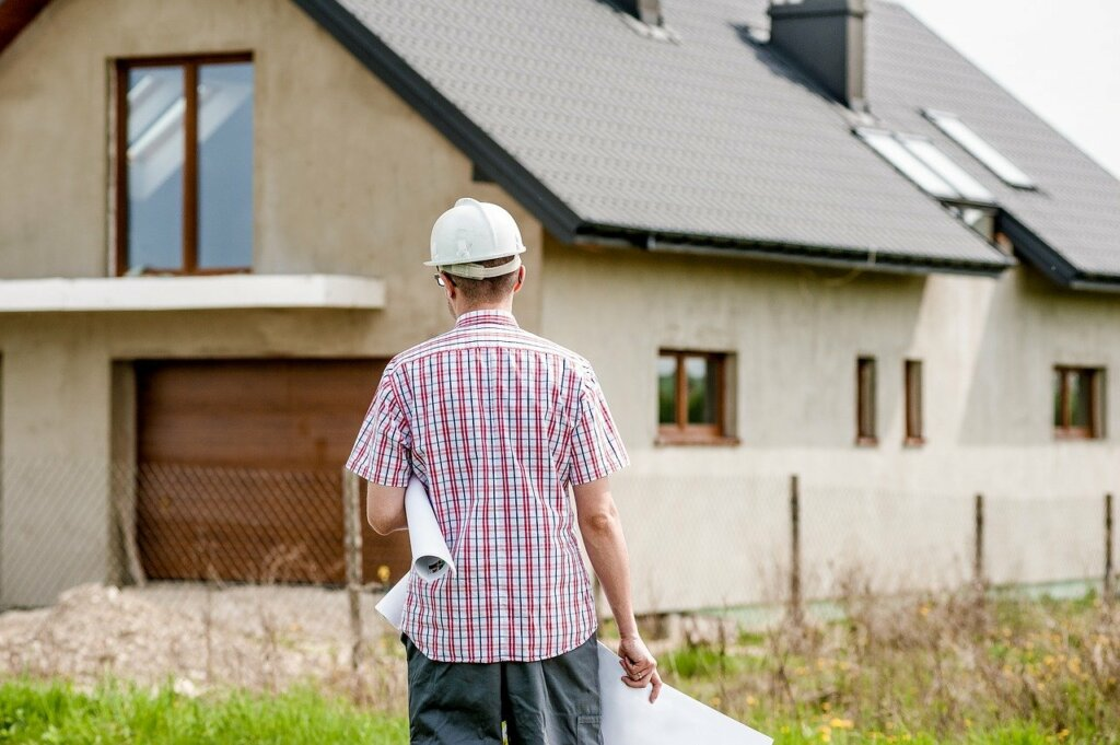 worker with hardhat looking at a house to repair