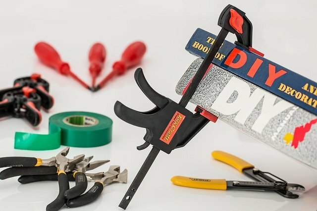 various repair DIY tools - pliers, repair tape, screwdrivers, and a DIY sign