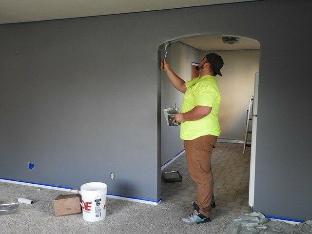 man in yellow shirt painting a home's interior wall gray