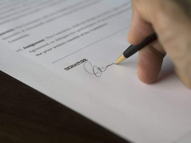 person signing their signature to a document