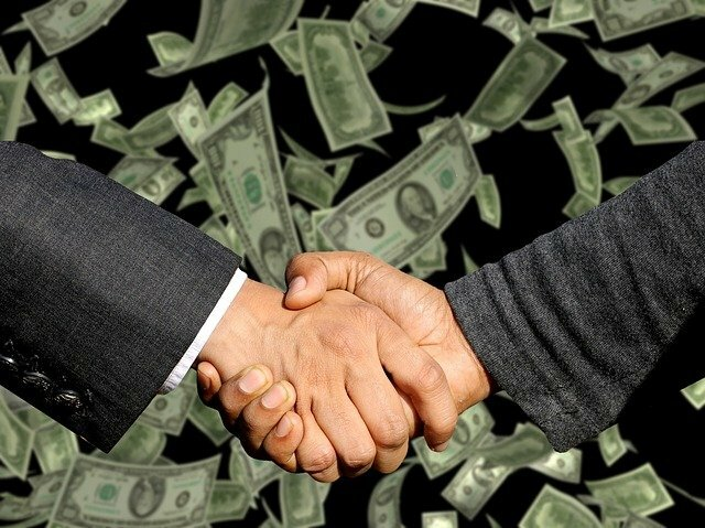 two hands shaking with a backdrop of dollar bills. Making a deal.