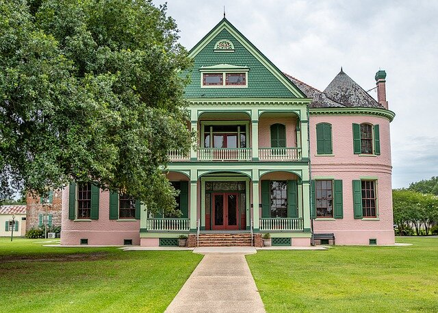 green and pink antebellum home with green lawn