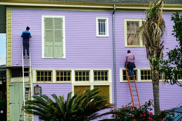 two workers on a ladder repairing the exterior of a house