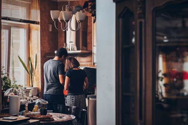 man and woman standing in front of a gas range in the kitchen