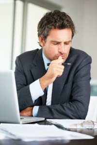 "Business man in deep thought with laptop thinking,""sell my house fast to the Aida Group."