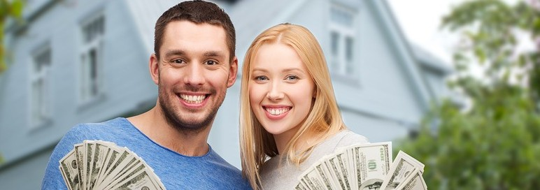 love, people, real estate, home and family concept - smiling couple showing dollar cash money over house background
