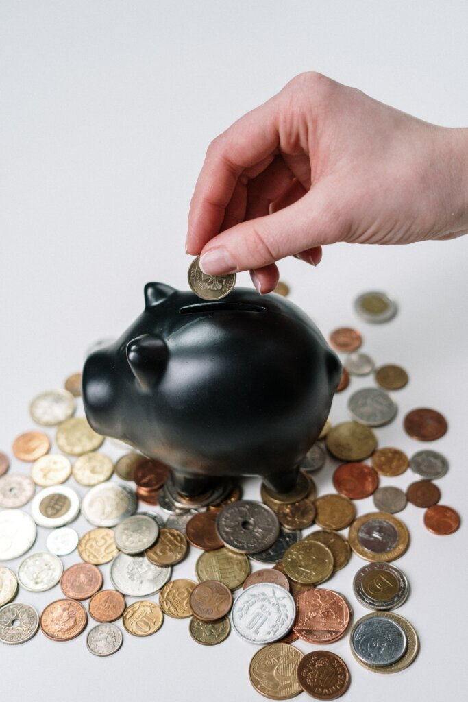 a piggy bank with coins all aroundd decorative purposes only