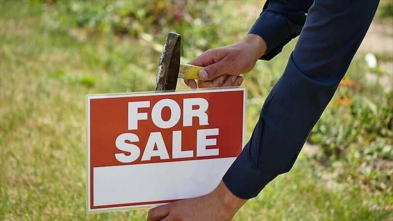 man hammering sign to sell house fast