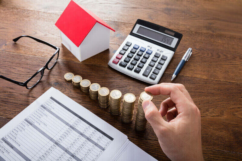 stacked coins, model house. calculator in a wooden table - capital tax concept