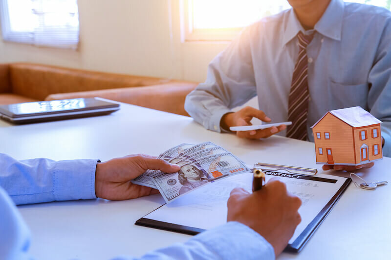 Cash House Buyer signing a contract or deed sale of a property sold as-is