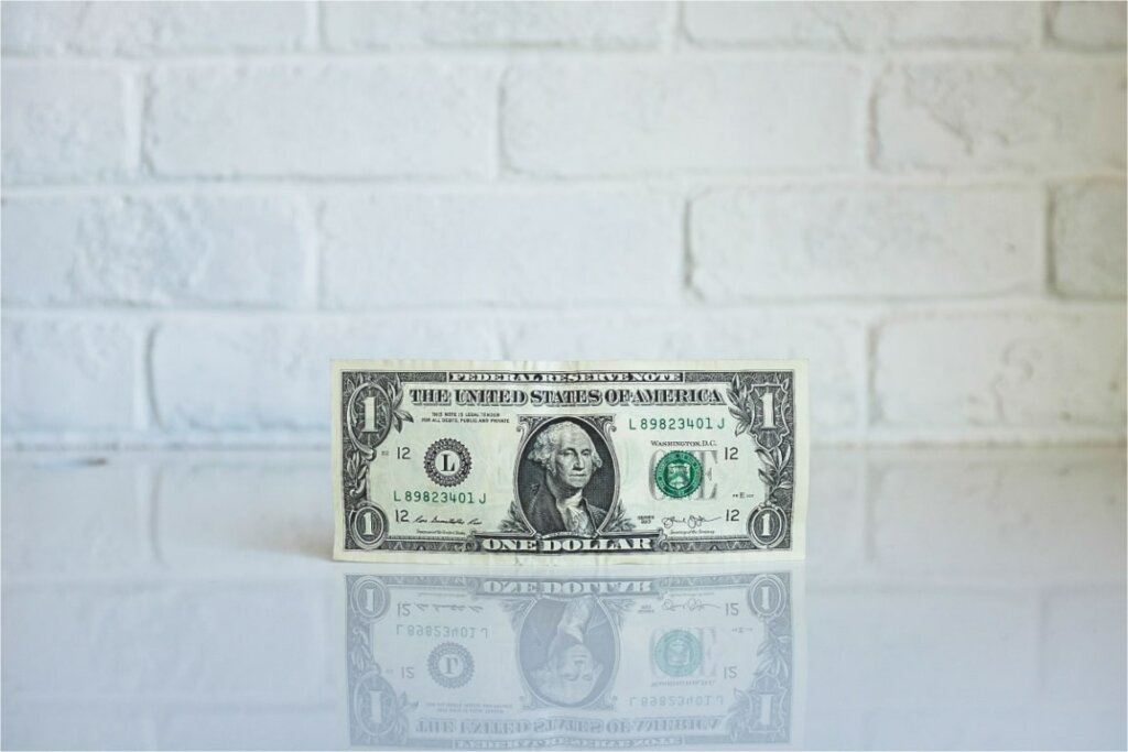 Dollar bill on a white table in front of a white brick wall