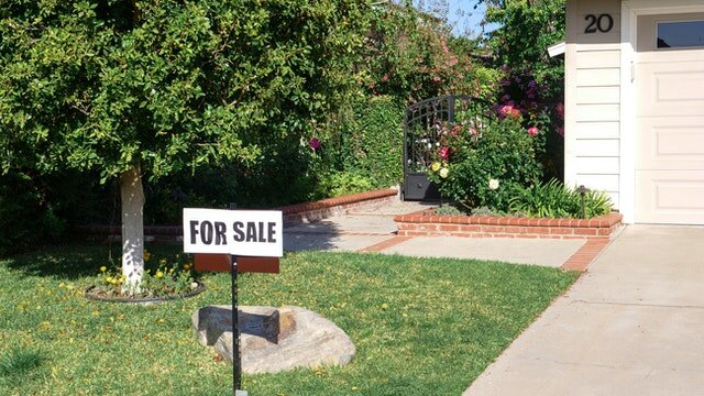 A for sale sign in front next to a driveway of a house