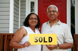 Older couple holding a sold sign saying Sell My House Quickly [market city]