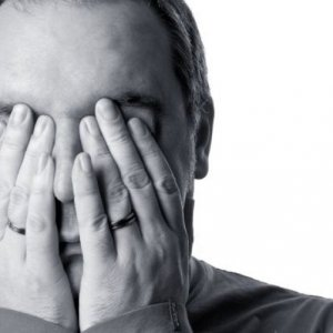 Man with hands over his face and stressed.