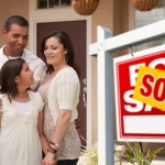 Hispanic Mother, Father and Daughter in Front of Their New Home with Sold Home For Sale Real Estate Sign.