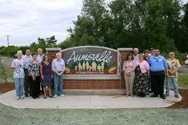 Aumsville City Sign with community members on each side.