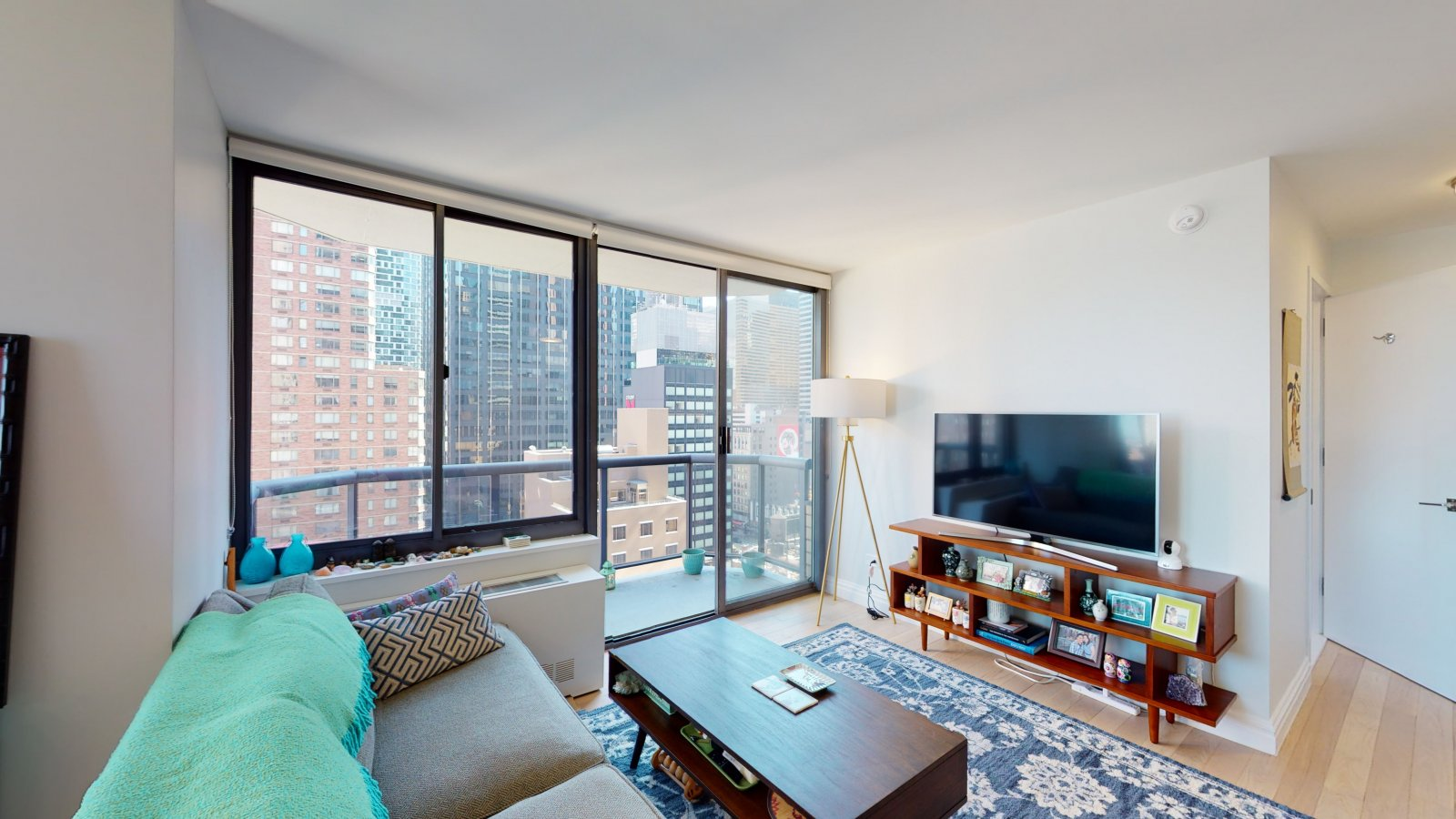235 W 48th Street Unit 22L Living room and balcony view of this Times Square adjacent rental apartment.